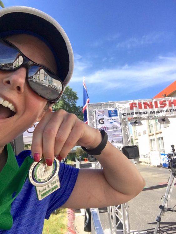 woman holding a medal after running a half-marathon