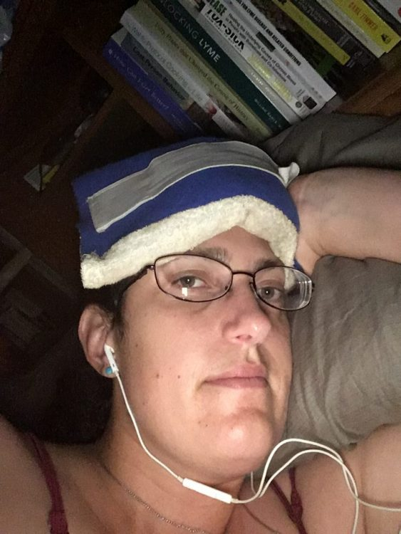 woman in bed with an ice pack on her head and earphones in