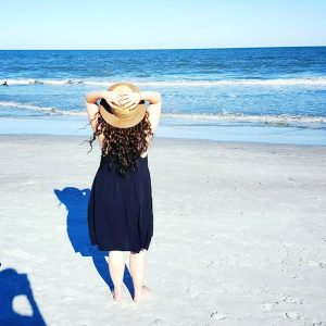 woman standing on the beach in a black sundress and hat