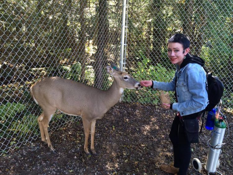 A young woman with oxygen feeds a deer.