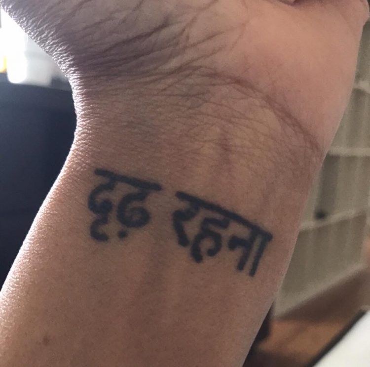 tattoo on a woman's wrist that says 'persevere' in hindi