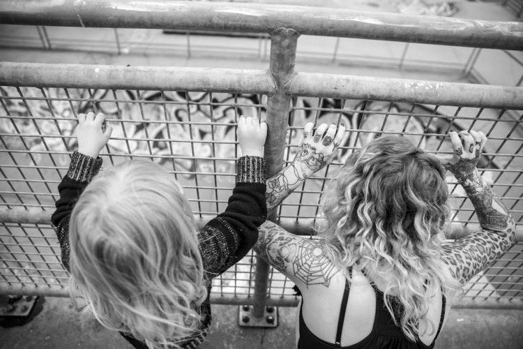 black and white photo of mother and son looking through wire fence