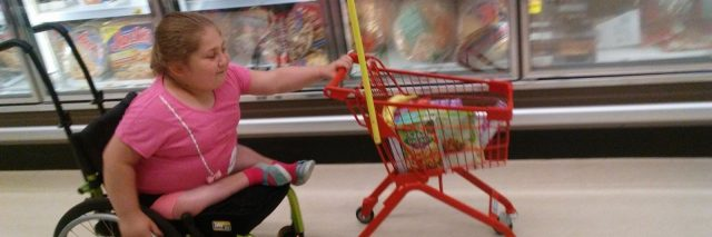 Namine pushing a shopping cart with one hand
