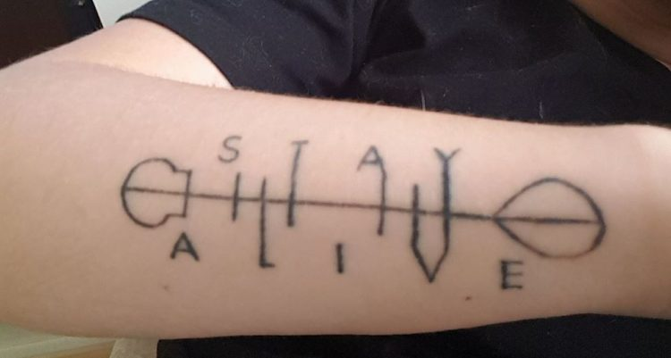 stay alive tattooed on forearm