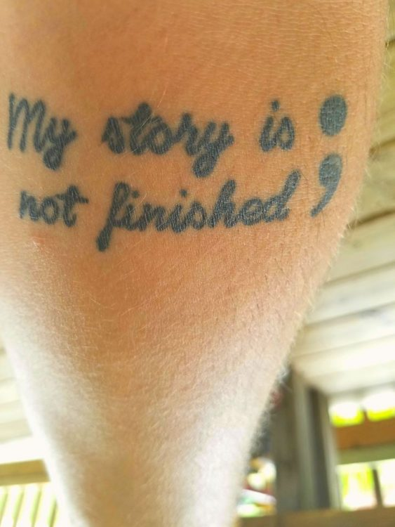 man with tattoo on his arm that says 'my story is not finished'