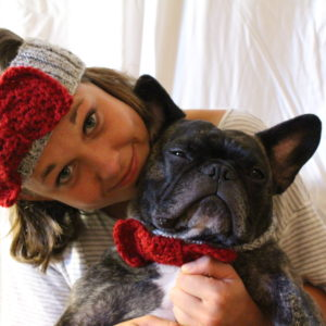 young woman wearing bandana holding dog
