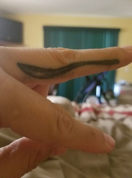 woman with a spoon tattoo on her finger