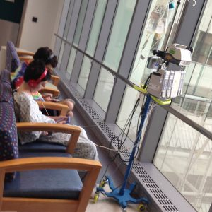 Two boys sitting in a hallway at a hospital, one boy has an IV and IV stand and hospital gown, they are playing video games