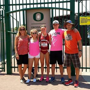 young woman with family in front of oregon university gates
