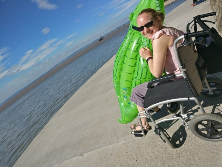 woman sitting in her wheelchair holding a pool float next to a lake