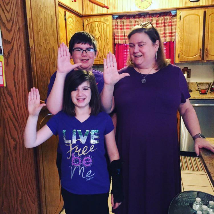 The writer with her two children, making the same hand gesture.