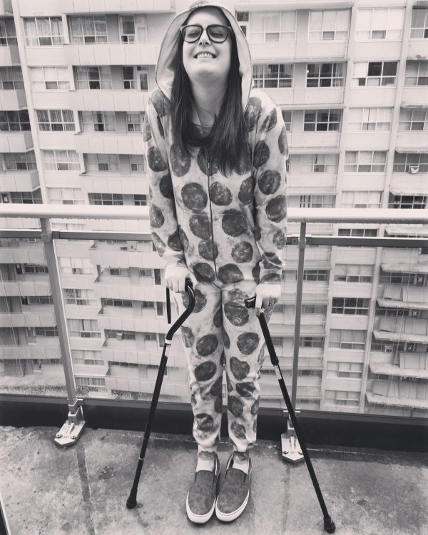 black and white photo of a woman in footie pajamas walking with two canes