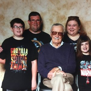 amanda's family posing in marvel shirts with stan lee