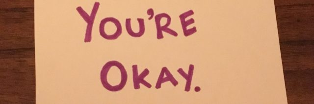 post it note on wooden table in pink text with words you're okay