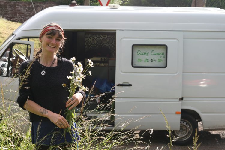 woman picking wildflowers on the side of the road next to the van