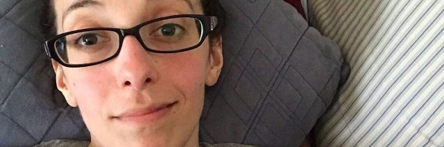 selfie of a woman lying on her couch and wearing glasses