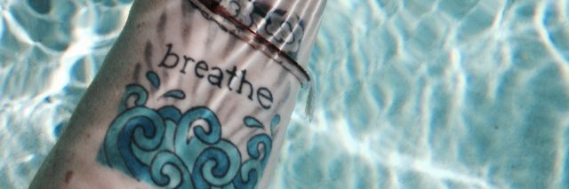woman's hand under water with a tattoo on her wrist that says 'breathe'