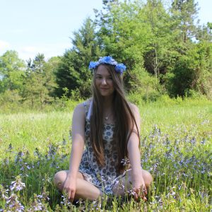 woman wearing flower crown and sitting cross-legged in a field