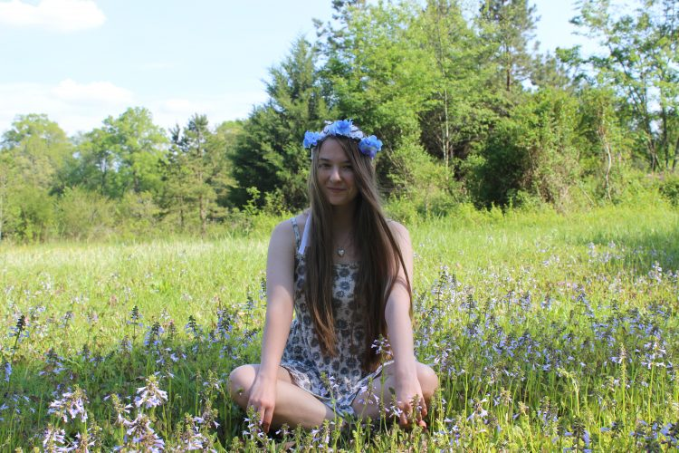woman wearing flower crown and sitting cross-legged in a field