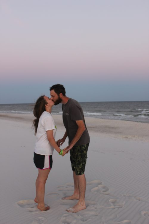 wife and husband kissing on the beach at sunset