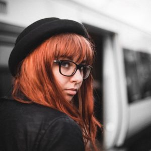 Lauren Hooper, red-haired woman wearing a black cap. Subway car in background.