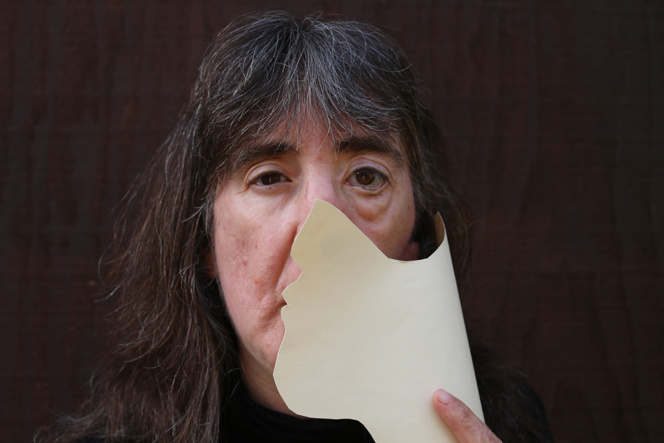 the author, holding a paper over one side of her face