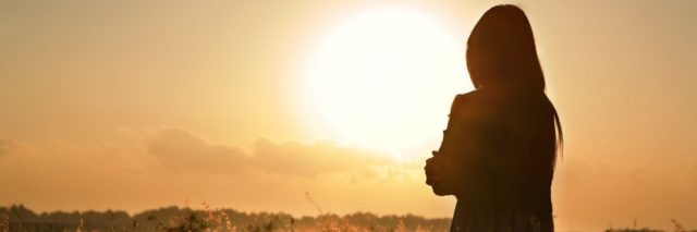 Woman standing in field, facing sun in sky