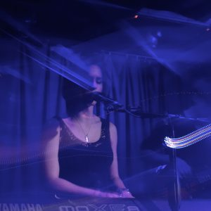 a woman playing piano and singing on a dark stage