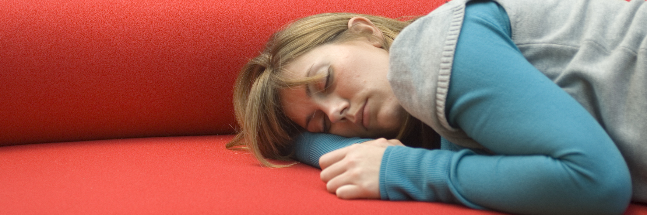 A woman sleeps on a red sofa.