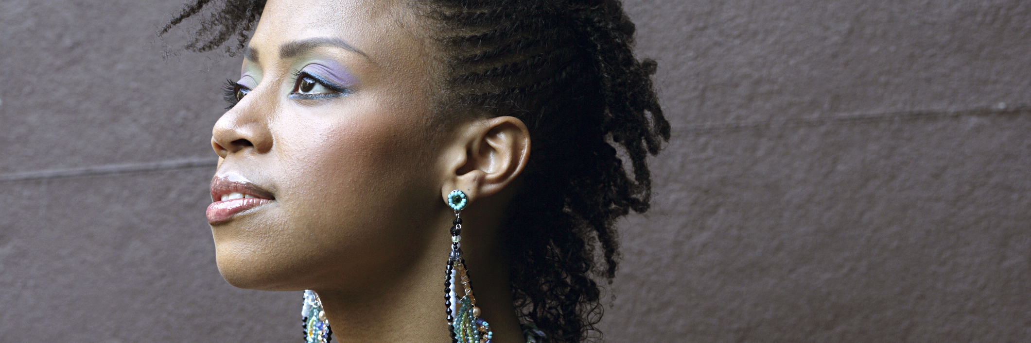 portrait of a woman with colorful earrings looking off into the distance