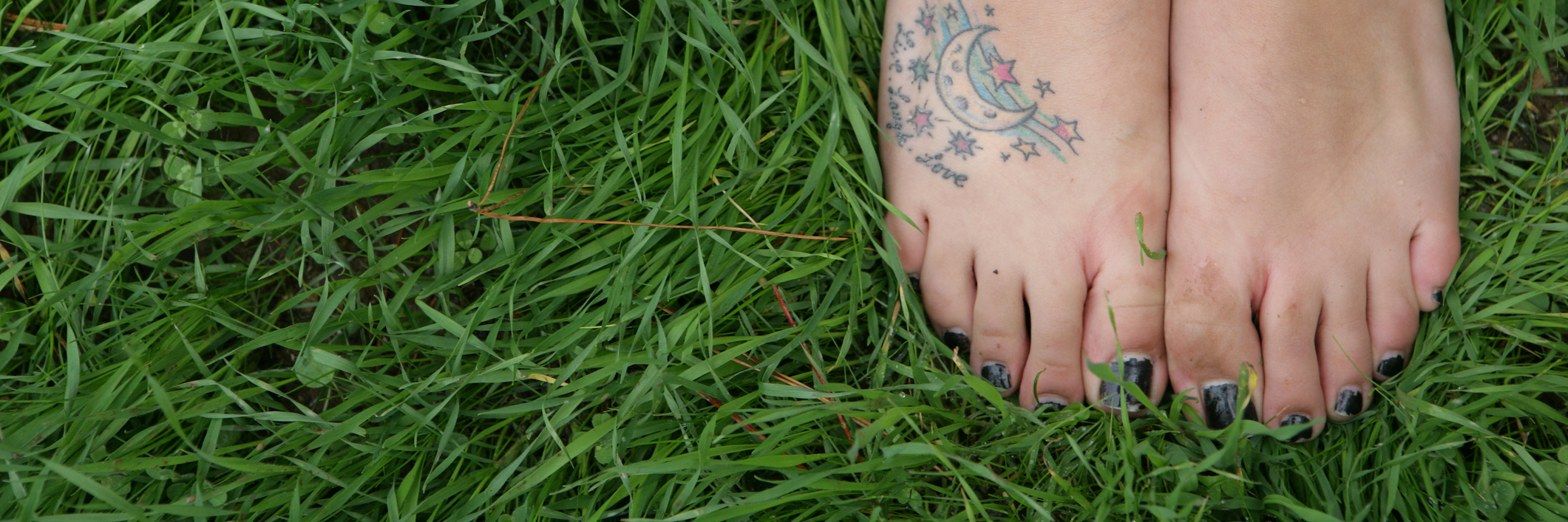 High angle view of woman's barefeet with tattoo.