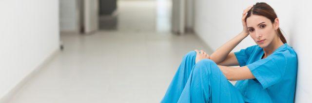 A nurse sitting on hospital floor.