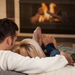 man and woman relaxing on their couch at home in front of a fireplace