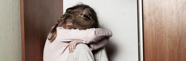 Sad girl with pajamas hiding in the closet