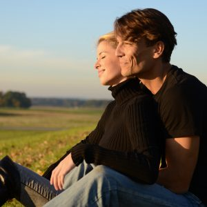 couple sitting together outside in a field and laughing