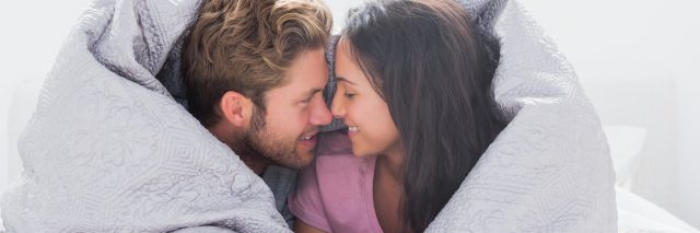 couple lying in bed wrapped in a duvet cover and smiling at each other