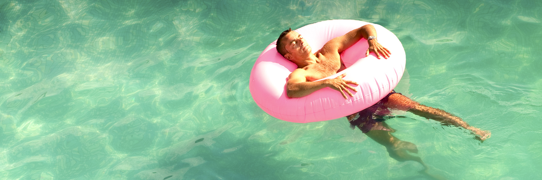 man lying in pink rubber ring in pool on summer day