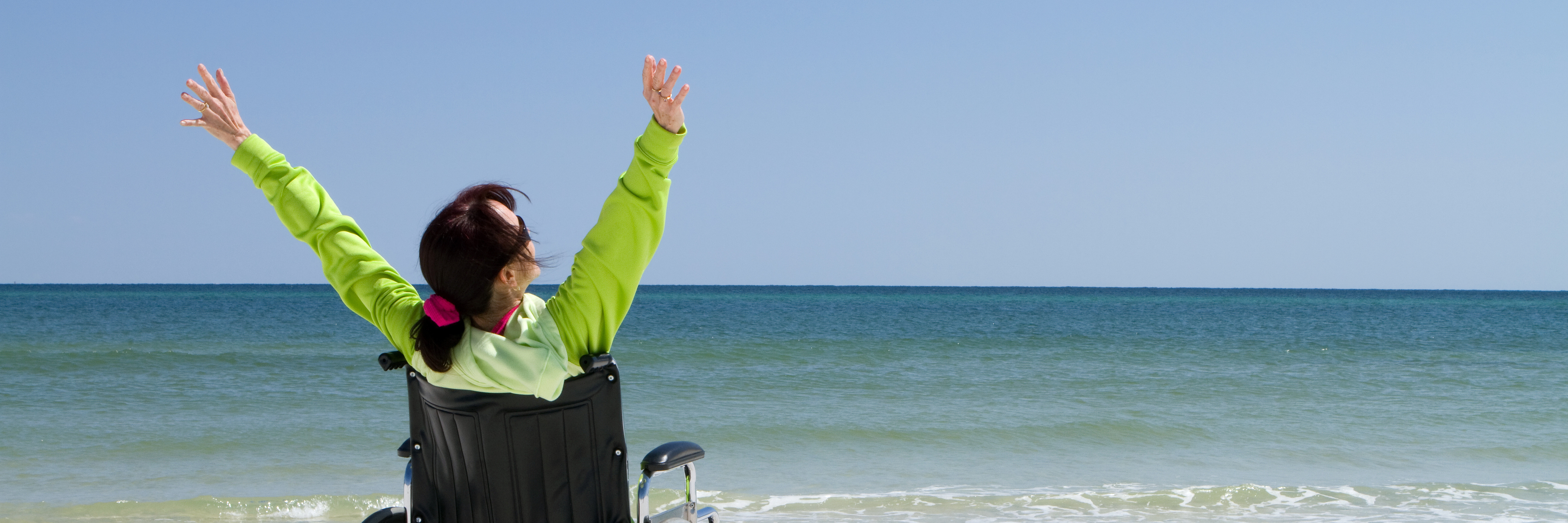 Woman in a wheelchair on the beach.