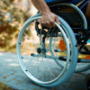 Close-up of male hand on wheel of wheelchair during walk in park.