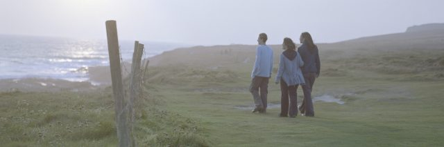 Woman with son and daughter (15-17) on grass by sea, rear view