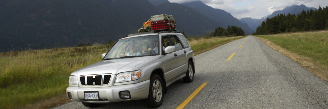 Car on a road trip with suitcases on roof.