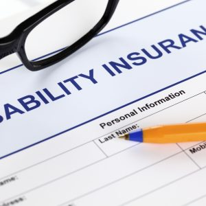 Disability form with glasses and ballpoint pen.
