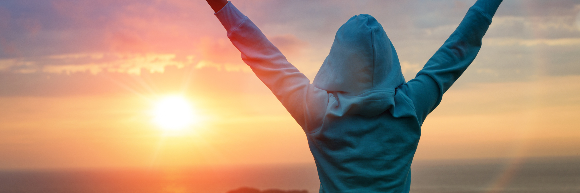 woman raising her arms in victory while looking at a sunset