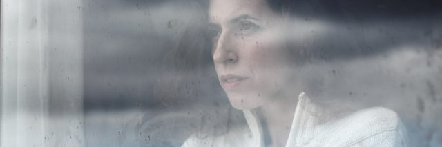 woman looking out her window on a cloudy day