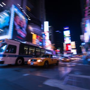 A long exposure night shot of a bus and a yellow cab driving through Times Square, NYC.