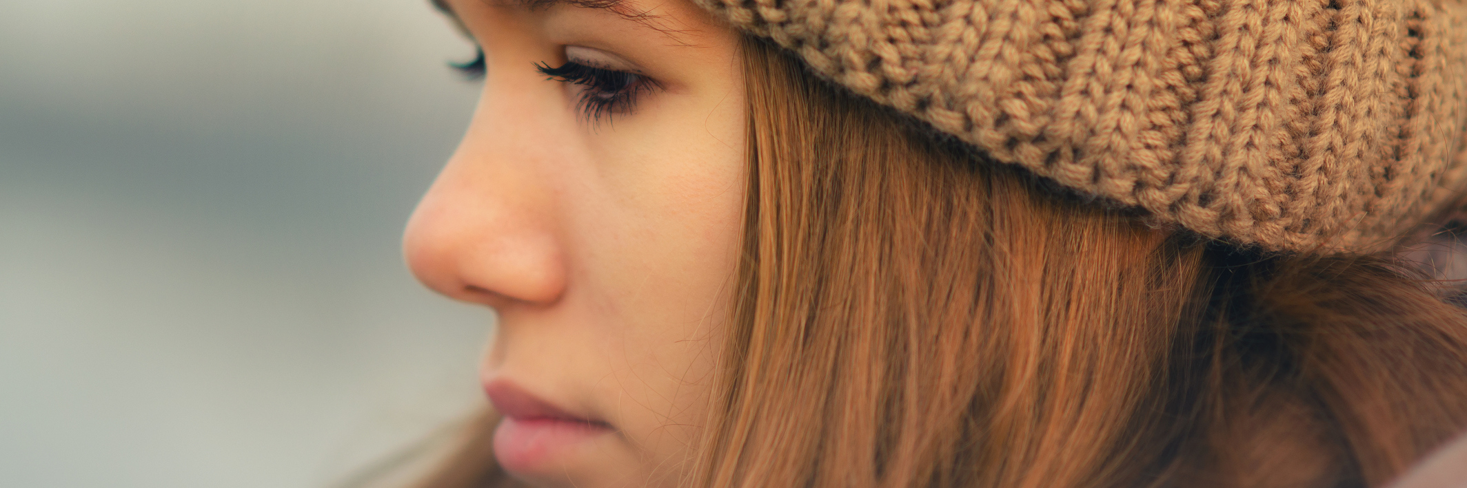 young woman wearing a hat looking sad