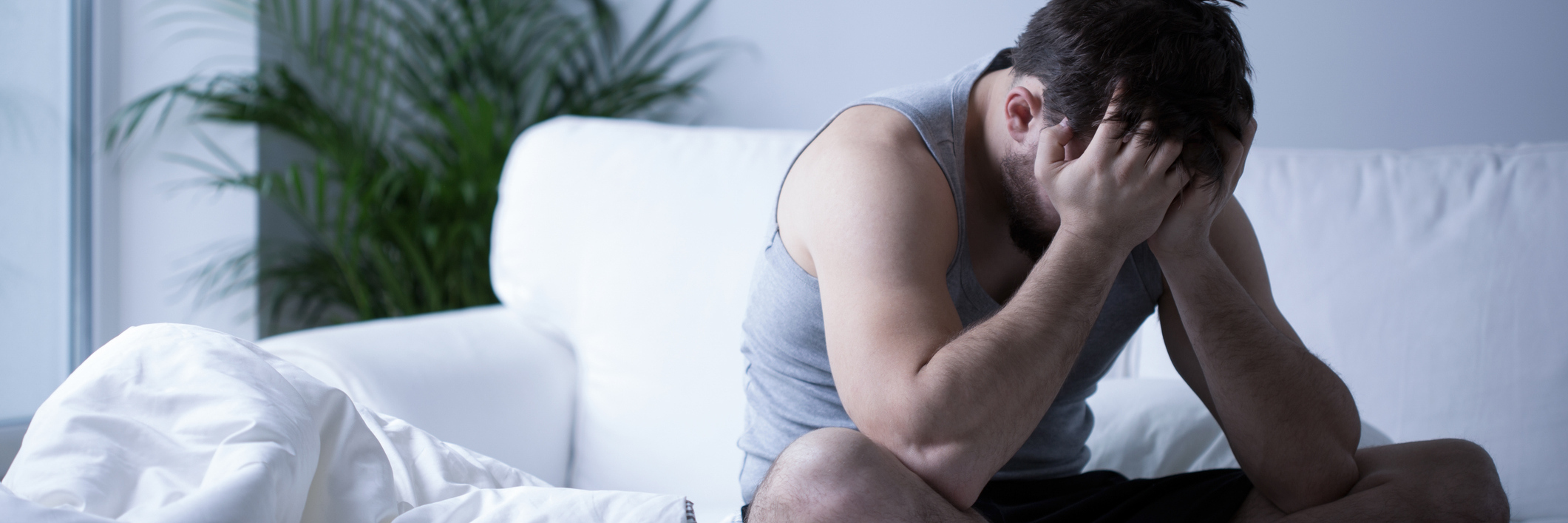 young man sitting on bed depression