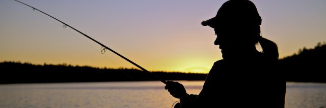 A woman fishing, silhouetted in the sunset.