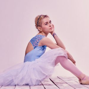 Tired ballet dancer sitting on the wooden floor, with a pink background behind her.