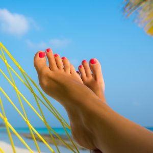 woman's feet in a hammock on the beach